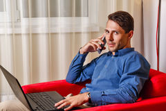 Man is working at a laptop and talking on a cell phone call. Royalty Free Stock Photos