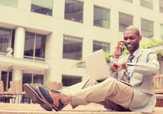 Man working on laptop talking on mobile phone outdoors Stock Photo