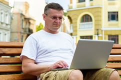 Man working on laptop in town. Middle-aged man in glasses sitting on a wooden bench in an urban environment working on his laptop Royalty Free Stock Photo