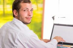 Man working on laptop turning around towards Royalty Free Stock Photo