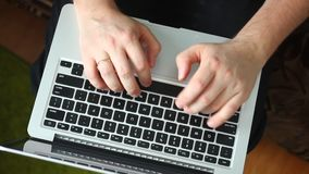 A man is working with a laptop. Type the text on the keyboard. The laptop is on my lap. View from above. A man is working with a laptop. Type the text on the stock footage