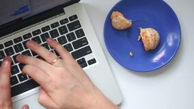 A man is working with a laptop. Type the text on the keyboard. From time to time, eating a mandarin lying on a saucer. View from a. Bove stock footage