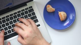 A man is working with a laptop. Type the text on the keyboard. From time to time, eating a mandarin lying on a saucer. There spits. Out bones. View from above stock video footage