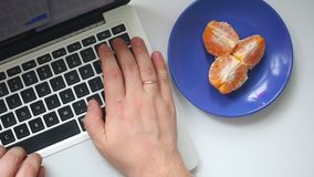 A man is working with a laptop. Type the text on the keyboard. From time to time, eating a mandarin lying on a saucer. View from a. Bove stock video footage