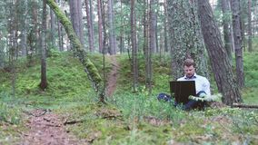 Man working on laptop under the tree in the forest. Young businessman working on laptop under the tree in the forest stock footage
