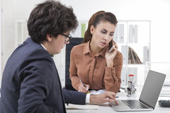 Man working at laptop, woman is on the phone Stock Image