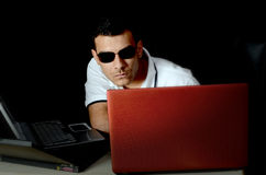 Man working with laptops. Man with dark eyeglasses working on laptop computers.  Theme:  computer hacking Royalty Free Stock Images