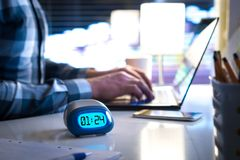 Man working late. Workaholic or being behind schedule concept. Business person in modern office building or home at night using laptop. Time in digital clock stock images