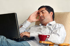 Man Working or learning from home. Tired man that works from home sleeps in front of his laptop.Concept photo of working from home, home jobs,distance education Stock Image