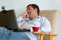 Man Working or learning from home. Tired man that works from home sleeps in front of his laptop.Concept photo of working from home, home jobs,distance education Stock Images