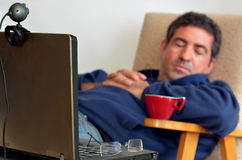 Man Working or learning from home. Tired man that works from home sleeps in front of his laptop.Concept photo of working from home, home jobs,distance education Stock Photography