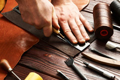 Man working with leather. Using crafting DIY tools Stock Photography
