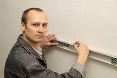 Man working level. Master measures the wall Stock Photography