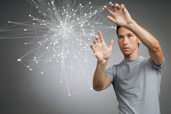 Man working with linked dots. Wireless connection concept. Young man in t-shirt working with linked dots on grey background. Wireless connection or global royalty free stock photography