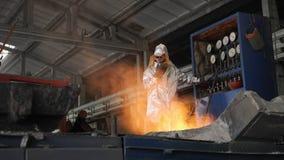 Man working with liquid metal in factory. Metal factory sparks. Man working with liquid metal in factory stock video