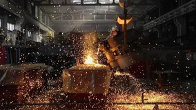 Man working with liquid metal in factory. Metal factory sparks. Man working with liquid metal in factory stock video footage