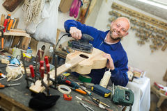 Man working on a machine at guitar workshop Royalty Free Stock Photo