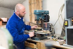 Man working on a machine at guitar workshop Stock Images