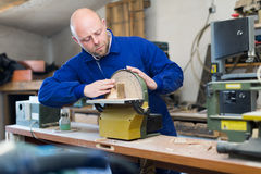 Man working on a machine at guitar workshop Royalty Free Stock Photos