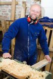 Man working on a machine at wood workshop Stock Image