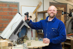 Man working on a machine at wood workshop Royalty Free Stock Photography