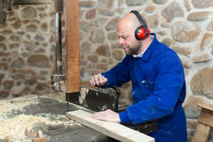 Man working on a machine at wood workshop Stock Images