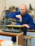 Man working on a machine at wood workshop Royalty Free Stock Photo
