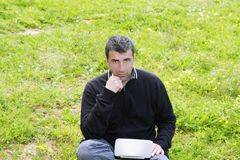 Man working on meadow grass notebook computer Royalty Free Stock Photos