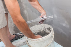 Man working with a metal spatula and prepared grout or adhesive when doing plaster. Man working with a metal spatula and prepared grout or adhesive when doing Stock Images