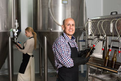 Man working on modern brewery. Cheerful  smiling mature men working on modern beer production facility Royalty Free Stock Photos