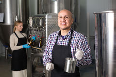 Man working on modern brewery. Joyful smiling mature men working on modern beer production facility Stock Photography
