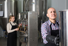 Man working on modern brewery. Positive  smiling mature men working on modern beer brewery Royalty Free Stock Photo