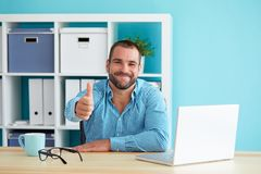 Man working in modern office and gesturing thumb up royalty free stock photography