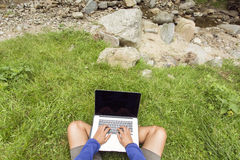 Man working in nature on his laptop over green grass Stock Image