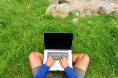 Man working in nature on his laptop over green grass Royalty Free Stock Image
