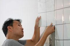 Bathroom tiles renovation. A man working at new bathroom tiles, putting them on the wall. HOME BUILDING & RENOVATION Stock Images