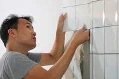 Bathroom tiles renovation. A man working at new bathroom tiles, putting them on the wall. HOME BUILDING & RENOVATION Stock Photos