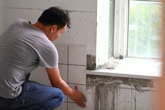 Bathroom tiles renovation. A man working at new bathroom tiles, putting them on the wall. HOME BUILDING & RENOVATION Stock Photography