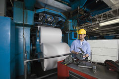 Man Working In Newspaper Factory. Young man in hardhat working in newspaper factory Stock Photography