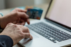 Man working on notebook with credit card. Stock Images