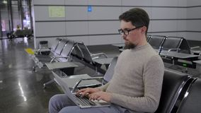 Man is working with notebook in departure lounge stock video