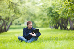 Man working with notebook in the park. Middle-aged businessman working with notebook in the park Stock Image