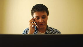 Man working on a notebook and talking on a phone stock footage