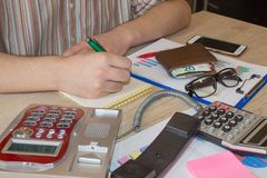 Man working on office desk with Calculator, a computer, a pen and document. Man, counting money and making calculations. Businessman working on office desk with royalty free stock photos