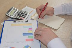 Man working on office desk with Calculator, a pen and document. Man, counting money and making calculations. Businessman working on office desk with Calculator royalty free stock photo
