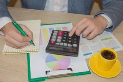 Man working on office desk with Calculator, a pen and document. Man, counting money and making calculations. Businessman working on office desk with Calculator stock image