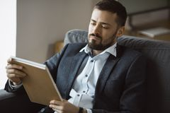 Man Working In Office Doing Notes. Confident concentrated handsome bearded businessman in a trendy suit reading important ideas in a notebook sitting on a sofa royalty free stock photos