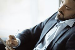 Man Working In Office Doing Notes. Confident concentrated handsome bearded businessman in a trendy suit writes down important ideas in a notebook sitting on a royalty free stock image