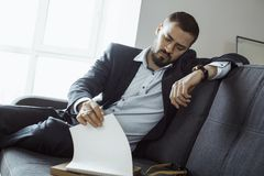 Man Working In Office Doing Notes. Confident concentrated handsome bearded businessman in a trendy suit writes down important ideas in a notebook sitting on a stock photos
