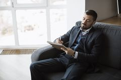 Man Working In Office Doing Notes. Confident concentrated handsome bearded businessman in a trendy suit writes down important ideas in a notebook sitting on a royalty free stock photos